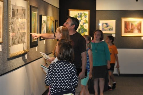 Guy Kelm with Kids and the Art of Writing class, studying the artwork for inspiration.