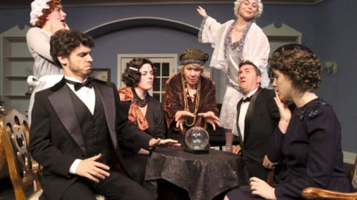 The cast of Blithe Spirit, played by Nicholas Kory (around the table from left), Kryston Wisely, Bri Keran, Barb McColgan, Kevin Yaeger and Brianna Engels, surround a table while holding a séance as they inadvertantly summon the titular spirit played by Nicole Rothleutner. (Kelly Humphrey, Brainerd Dispatch)
