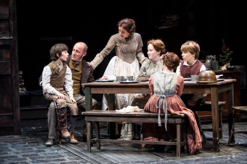 Kris L. Nelson (Bob Cratchit) and Virginia S. Burke (Mrs. Cratchit) with Zel Weilandgruber as (Tiny Tim), Ella R. Nelson (Martha), Tess Nelson (Belinda) and Noah Deets (Peter) Photo by Dan Norman