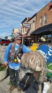 Mr. Happy and the Biker Chef posing with a buffalo outside the Chef's favorite breakfast place in Custer, SD.