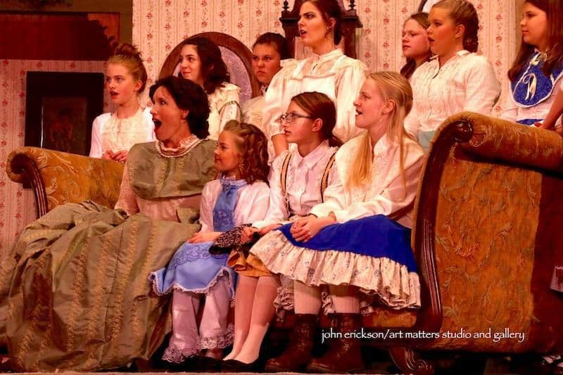 Jenn Abramson as Marmee, Sarah Ciesluk as Hannah, and the children's choir in Stage North's production of Little Women. Photo by John Erickson