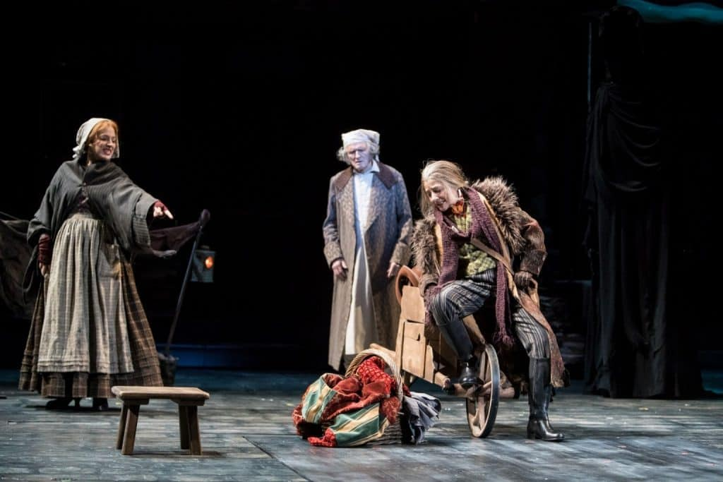 Emily Gunyou Halaas (Mrs. Dilber), Nathaniel Fuller (Ebenezer Scrooge) and Charity Jones (Old Joe) in the Guthrie Theater's production of A Christmas Carol by Charles Dickens, adapted by Crispin Whittell, directed by Lauren Keating. Scenic design by Walt Spangler, costume design by Mathew J. LeFebvre, lighting design by Christopher Akerlind. November 14 – December 30, 2017 on the Wurtele Thrust Stage at the Guthrie Theater, Minneapolis. Photo by Dan Norman.