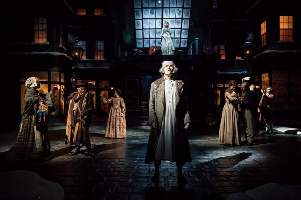 Nat Fuller as Scrooge and the cast of the Guthrie Theater's production of A Christmas Carol by Charles Dickens, adapted by Crispin Whittell, directed by Lauren Keating. Scenic design by Walt Spangler, costume design by Mathew J. LeFebvre, lighting design by Christopher Akerlind. November 14 – December 30, 2017 on the Wurtele Thrust Stage at the Guthrie Theater, Minneapolis. Photo by Dan Norman.