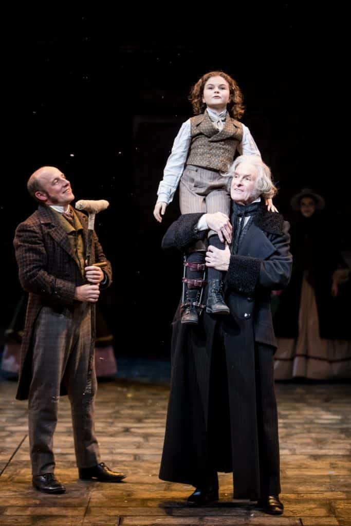 Kris L. Nelson (Bob Cratchit, Donald), Sophie Jones (Tiny Tim) and Nathaniel Fuller (Ebenezer Scrooge) in the Guthrie Theater's production of A Christmas Carol by Charles Dickens, adapted by Crispin Whittell, directed by Lauren Keating. Scenic design by Walt Spangler, costume design by Mathew J. LeFebvre, lighting design by Christopher Akerlind. November 14 – December 30, 2017 on the Wurtele Thrust Stage at the Guthrie Theater, Minneapolis. Photo by Dan Norman.