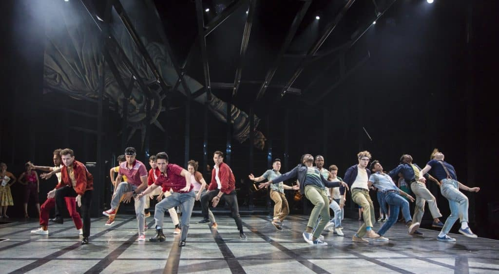 The cast of the Guthrie Theater's production of West Side Story, based on a conception of Jerome Robbins with a book by Arthur Laurents. Music by Leonard Bernstein, lyrics by Stephen Sondheim, directed by Joseph Haj. Scenic design by Christopher Acebo, costume design by Jen Caprio, lighting design by Bradley King, sound design by Elisheba Ittoop. June 16 – August 26, 2018 on the Wurtele Thrust Stage at the Guthrie Theater, Minneapolis. Photo by T Charles Erickson.