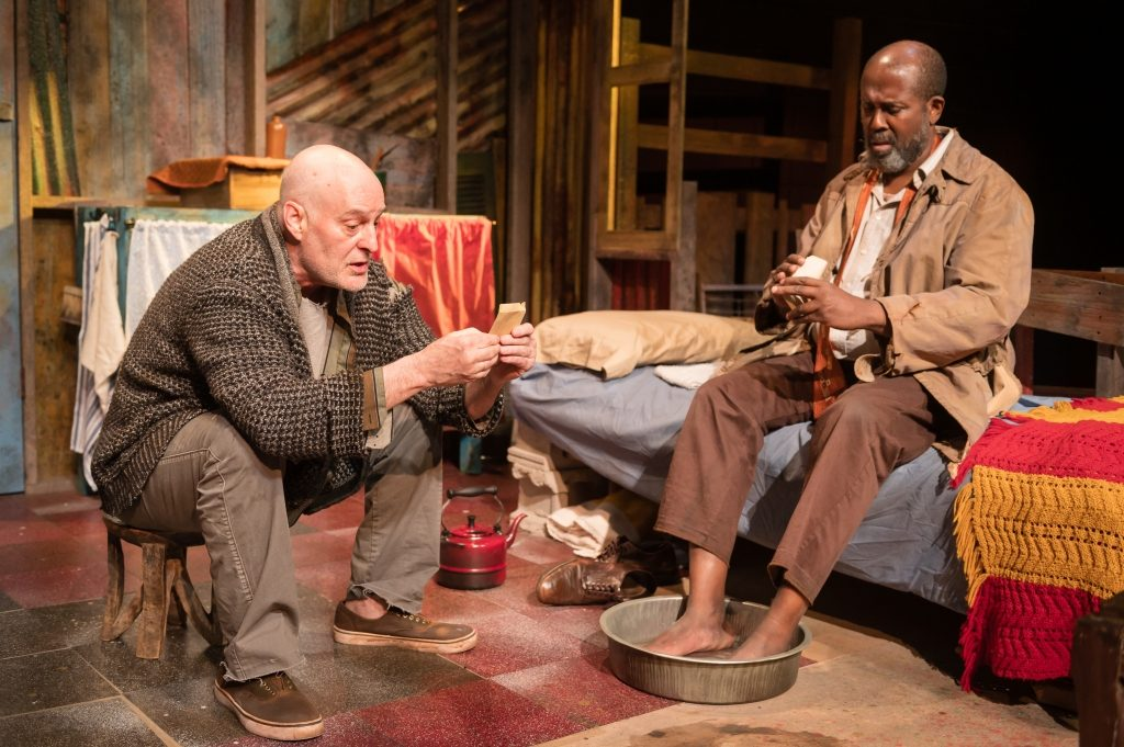 James A. Williams as Zachariah and Stephen Yoakam as Morris in Blood Knot at Pillsbury House Theatre. Morris is preparing a salt water soak for Zach's sore feet. Photo by Rich Ryan